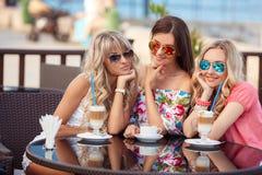 享用咖啡在咖啡馆的三名妇女 免版税库存照片