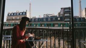 享用咖啡早餐的愉快的可爱的轻松的女实业家,使用智能手机在巴黎咖啡馆有埃菲尔铁塔视图 影视素材