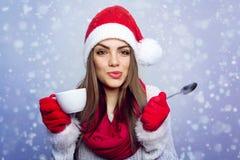 享用咖啡的圣诞老人女孩在冬天 库存照片