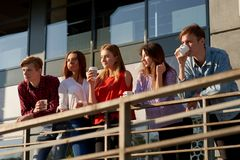 享用咖啡的学生去在街道上 免版税库存照片