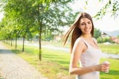 享用咖啡的愉快的少妇在公园 库存图片