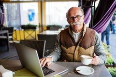 享用咖啡的活泼的老人画象,当与现代膝上型计算机一起使用在室外咖啡馆时桌上  免版税库存照片