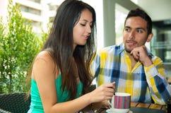 享用咖啡的西班牙逗人喜爱的夫妇在舒适期间 免版税库存图片