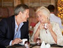 享用咖啡的资深夫妇在餐馆 免版税库存照片