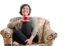享用咖啡的逗人喜爱的妇女 库存照片