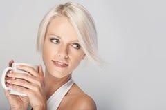 享用咖啡的年轻白肤金发的妇女 图库摄影