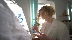 享用图画,有启发的跳舞的快乐的艺术家女孩绘与明亮的颜色的画在白色帆布  股票视频