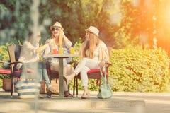享用在一个室外咖啡馆,友谊概念的女朋友鸡尾酒 库存照片