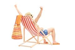 享用在一张海滩睡椅的愉快的人用被举的手 图库摄影