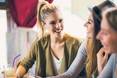 享用在交谈和饮用的咖啡的朋友 免版税库存照片