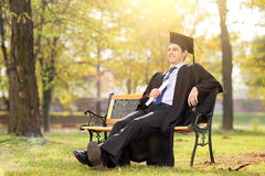 享用在公园的大学毕业生 免版税库存照片