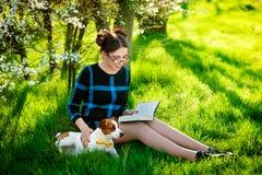 享用在公园的美丽的年轻深色的妇女户外与她华美的杰克罗素狗一起-读一本书 免版税库存照片