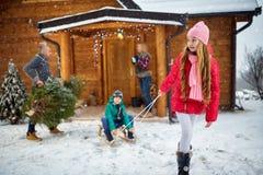 享用在冬天儿童sledding的家庭 库存图片