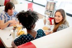 享用在吃饭的客人的年轻多种族朋友 库存照片