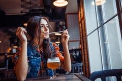 享用在咖啡馆的啤酒妇女一份新鲜的草稿 艺术处理 免版税图库摄影