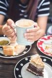 享用在咖啡馆的妇女拿铁咖啡 免版税图库摄影