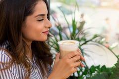 享用在咖啡馆的微笑的年轻女人画象早晨咖啡 免版税图库摄影