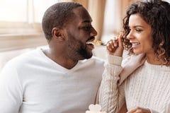 享用在咖啡馆的快乐的非裔美国人的夫妇杯形蛋糕 库存图片