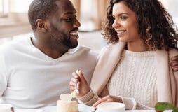 享用在咖啡馆的正面非裔美国人的夫妇杯形蛋糕 库存图片