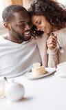 享用在咖啡馆的仔细的非裔美国人的夫妇点心 免版税库存图片