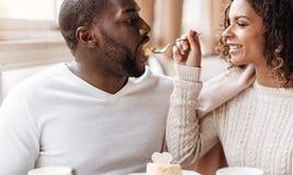 享用在咖啡馆的滑稽的非裔美国人的夫妇点心 免版税库存照片