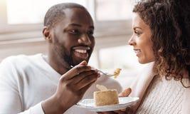 享用在咖啡馆的滑稽的非裔美国人的夫妇点心 库存图片