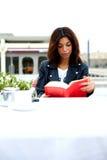 享用在咖啡馆的Attractie女性行家一本好书在她的休闲时间周末 库存图片