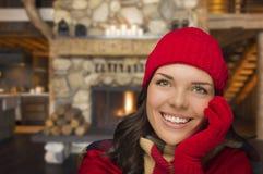 享用在土气客舱的华美的混合的族种女孩温暖的壁炉 免版税图库摄影