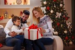 享用在圣诞节礼物的家庭 库存照片