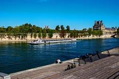 享用在塞纳河,巴黎的堤防的人们太阳 库存图片