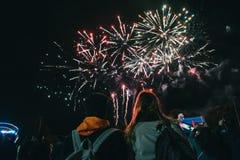 享用在夜空的两个女性朋友美丽的明亮的五颜六色的烟花 免版税图库摄影