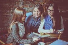 享用在学会的三个女孩在咖啡馆 免版税图库摄影