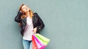 享用在巨大购物以后的时髦的女孩 拿着购物带来的顾客妇女 摆在对灰色墙壁,拷贝空间的女孩 库存图片