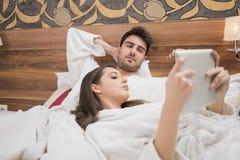享用在床上的美好的愉快的年轻夫妇在温泉以后 夫妇我 库存照片