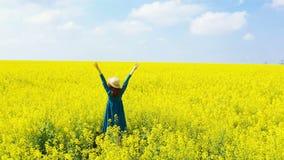 享用在开花的油菜籽领域的美女 股票录像