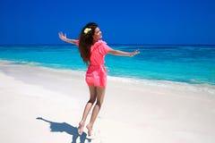 享用在异乎寻常的海滩的女孩 跳跃在的愉快的少妇 库存图片