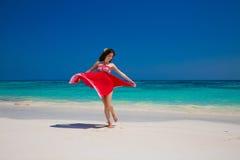 享用在异乎寻常的海滩的美好的愉快的妇女跳舞在夏天 免版税图库摄影