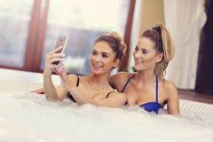 享用在旅馆温泉的愉快的女朋友极可意浴缸 图库摄影