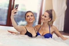 享用在旅馆温泉的愉快的女朋友极可意浴缸 免版税库存图片