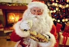 享用在曲奇饼和牛奶的圣诞老人 免版税库存照片