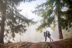 享用在有雾的森林山行迹的男人和妇女背包徒步旅行者 库存图片