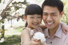 享用在树的微笑的父亲和女儿樱花在公园春天,拿着花的女儿 库存照片