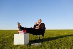 享用在椅子的商人咖啡在象草的领域反对天空 免版税库存图片