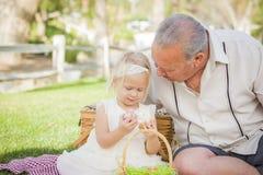 享用在毯子的祖父和孙女复活节彩蛋在 免版税库存图片