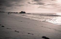享用在沙滩的人剪影与波浪热的晴天在大西洋海岸的10月 图库摄影