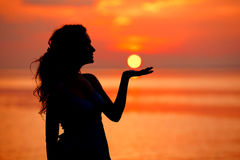 享用在海日落的愉快的妇女 现出轮廓反对太阳 免版税库存照片