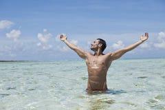 享用在海滩的水中的人 库存图片
