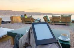 享用在海滩的一个e书e读者 免版税库存照片