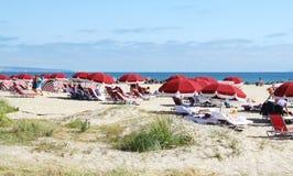 享用在海滩的度假者 库存照片