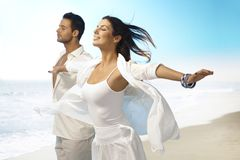 享用在海滩的年轻夫妇夏天太阳 图库摄影
